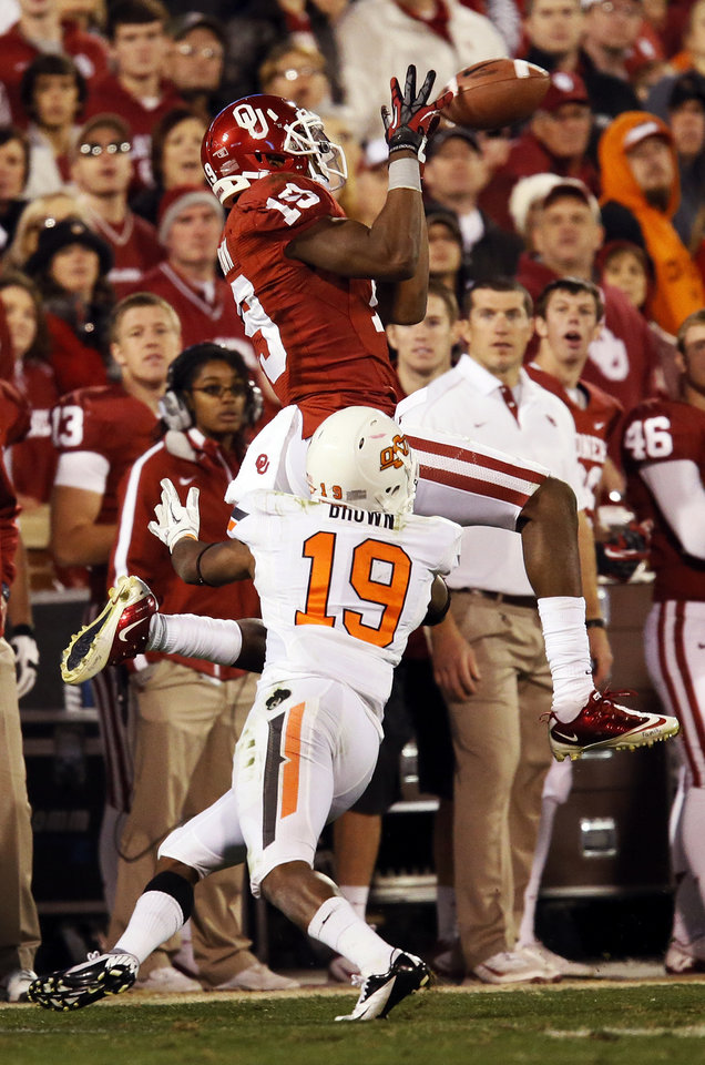 Photo - Oklahoma's Justin Brown (19) catches a pass against Oklahoma State's Brodrick Brown (19) in the fourth quarter during the Bedlam college football game between the University of Oklahoma Sooners (OU) and the Oklahoma State University Cowboys (OSU) at Gaylord Family-Oklahoma Memorial Stadium in Norman, Okla., Saturday, Nov. 24, 2012. OU won, 51-48 in overtime. Photo by Nate Billings , The Oklahoman