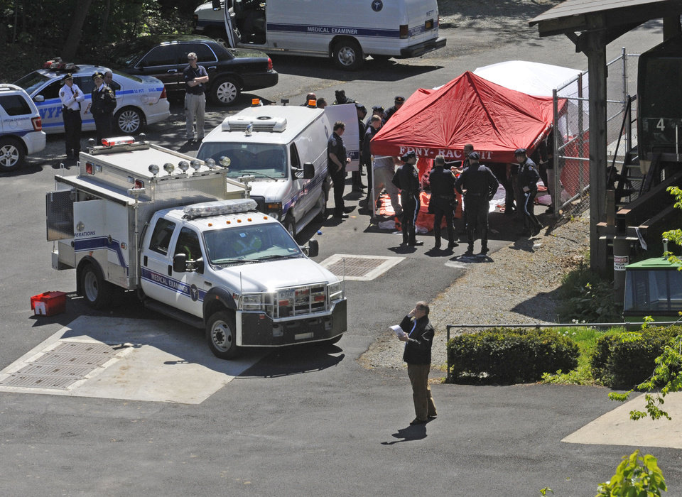 Photo -   Police surround a temporarily built tent where the victims of the vehicle crash were brought, Sunday April 29, 2012, in New York. Authorities say an out-of-control van plunged off a roadway near the Bronx Zoo, killing seven people, including three children. (AP Photo/ Louis Lanzano)