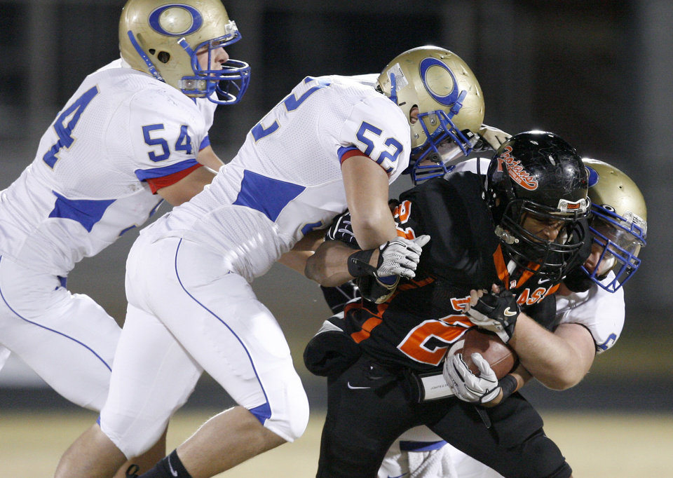 Ian Robinson of Douglass is brought down by Oologah's Garrett Martin, left, Kole Koenig, and Aaron Thompson during a high school football playoff game in Oklahoma City, Friday, Nov. 19, 2010.  Photo by Bryan Terry, The Oklahoman