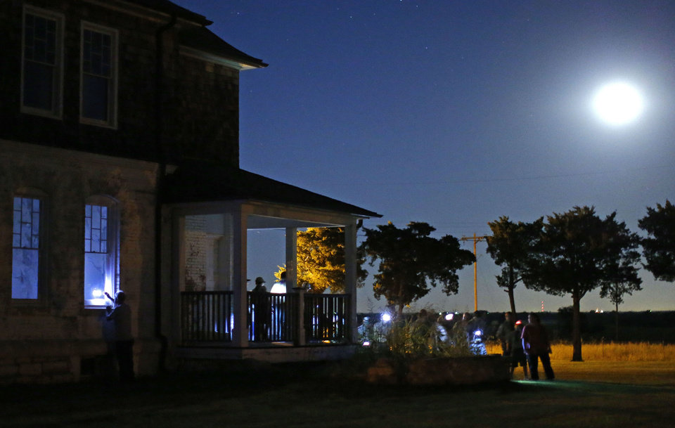 Photo -  A crowd gathers around the officers' quarters during a guided ghost tour by lantern light around Fort Reno in El Reno on Saturday, Sept. 21, 2013. Photo by Bryan Terry, The Oklahoman