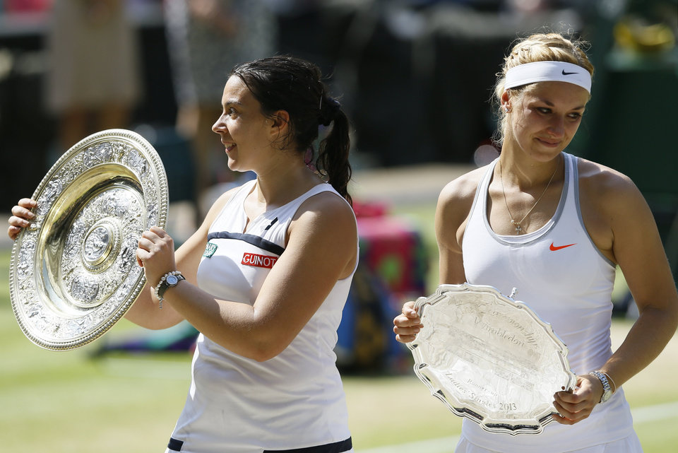 Marion Bartoli of France, left, and Sabine Lisicki of Germany pose during the trophy ceremony after Bartoli won the Women's singles final match against at the All England Lawn Tennis Championships in Wimbledon, London, Saturday, July 6, 2013. (AP Photo/Kirsty Wigglesworth)
