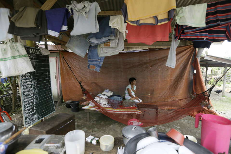 A flash flood survivor makes use of a waiting shed as a temporary shelter after Typhoon Bopha destroyed most of the houses in the area in New Bataan township, Compostela Valley in the southern Philippines, Thursday, Dec. 6, 2012.  The powerful typhoon that washed away emergency shelters, a military camp and possibly entire families in the southern Philippines has killed hundreds of people with nearly 400 missing, authorities said Thursday. (AP Photo/Bullit Marquez)