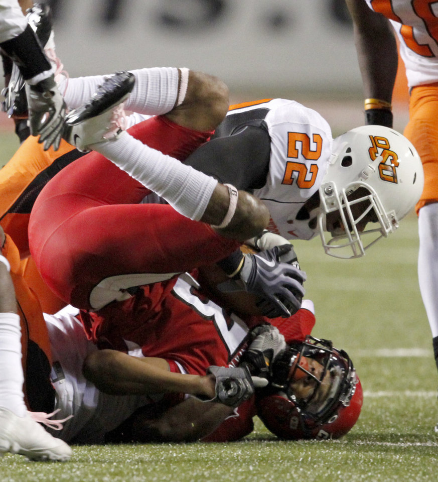 Photo - OSU's James Thomas brings down  Louisiana-Lafayette's Pierre Hill during the football game between the University of Louisiana-Lafayette and Oklahoma State University at Cajun Field in Lafayette, La., Friday, October 8, 2010. Photo by Bryan Terry, The Oklahoman