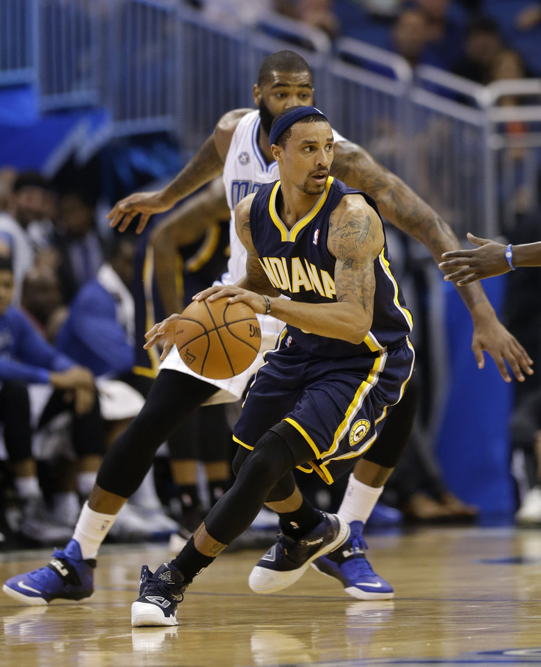 Photo - Indiana Pacers' George Hill, front, makes a move to get around Orlando Magic's Kyle O'Quinn during the first half of an NBA basketball game in Orlando, Fla., Wednesday, April 16, 2014. (AP Photo/John Raoux)