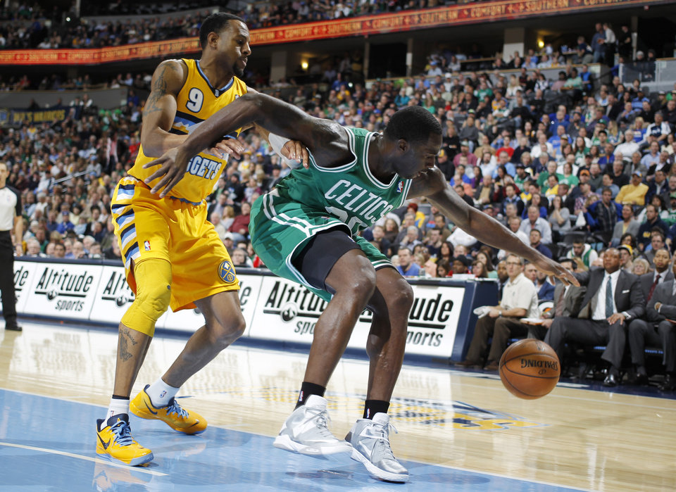 Boston Celtics forward Brandon bass, right, reaches out to recover a loose ball as Denver Nuggets guard Andre Iguodala covers in the first quarter of the Nuggets' 97-90 victory in an NBA basketball game in Denver on Tuesday, Feb. 19, 2013. (AP Photo/David Zalubowski)
