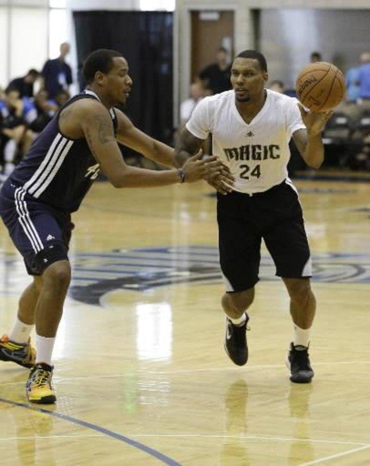 Orlando Magic's Romero Osby passes the ball around Oklahoma City Thunder's Ron Anderson during an NBA summer league basketball game, Monday, July 8, 2013, in Orlando, Fla. (AP Photo/John Raoux)