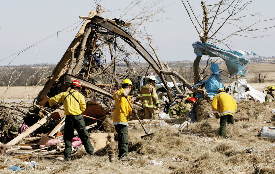 Photo - Searchers look through mobile home debris for unaccounted persons on Brock Road in Lone Grove, Wednesday, Feb. 11, 2009. The rails in the tree are the base of a mobile home. BY PAUL B. SOUTHERLAND, THE OKLAHOMAN