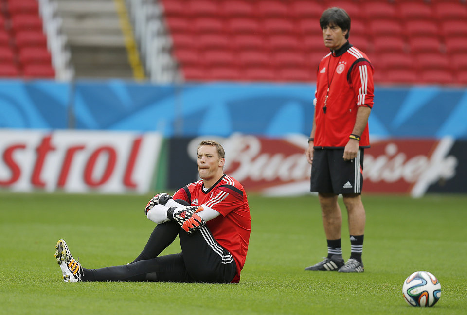 Photo - Germany's goalkeeper Manuel Neuer, left, stretches while Germany's head coach Joachim Loew watches  during a training session at the Estadio Beira-Rio Stadium in Porto Alegre, Brazil, Sunday, June {try}, 2014.  Germany will play Algeria in a World Cup round of 16 soccer match on June 30. (AP Photo/Frank Augstein)