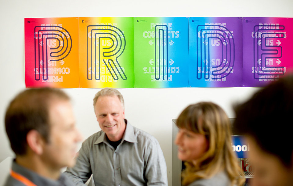 Photo - In this  Wednesday, Feb. 12, 2014, photo, workers from Facebook's health center gather near a banner promoting gay pride at the company's Menlo Park, Calif., headquarters. The social media giant is adding a customizable profile option with about 50 different terms people can use to identify their gender. (AP Photo/Noah Berger)