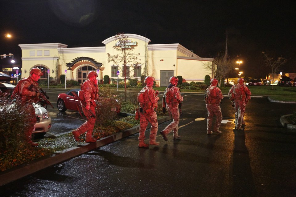 Photo - A tactical team moves through the mall parking lot at Clackamas Town Center in Portland, Ore., Tuesday, Dec. 11, 2012. Witnesses say the scene went from cheery to chaotic in seconds when a gunman opened fire in the suburban Portland shopping mall Tuesday, killing two people and wounding another. (AP Photo/The Oregonian, Thomas Boyd)
