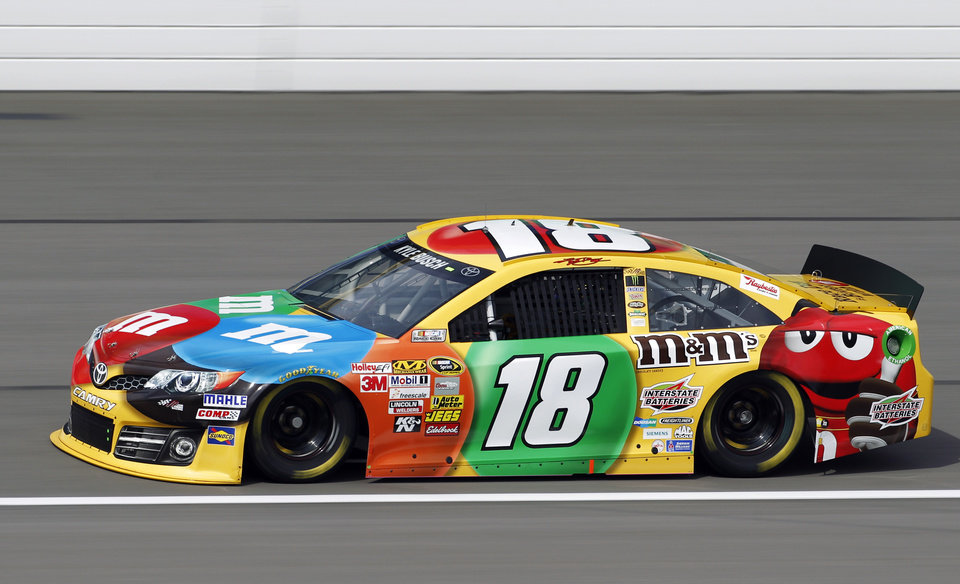 Photo - Driver Kyle Busch takes a lap during practice for Sunday's NASCAR Sprint Cup series auto race at Kansas Speedway in Kansas City, Kan., Friday, Oct. 4, 2013. (AP Photo/Colin E. Braley)