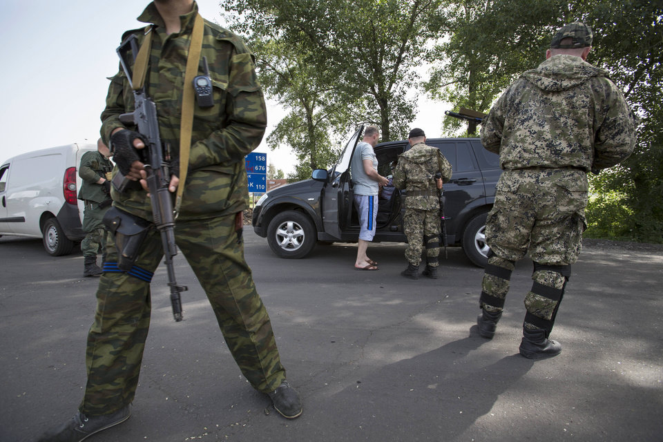 Photo - Pro-Russian armed militants guard a checkpoint blocking the major highway which links Kharkiv, outside Slovyansk, eastern Ukraine, Monday, May 19, 2014. Lawmakers and officials from eastern Ukraine on Saturday poured criticism on the fledging central government, accusing it of ignoring legitimate grievances of the regions which have been overrun by pro-Russia militia fighting for independence. (AP Photo/Alexander Zemlianichenko)