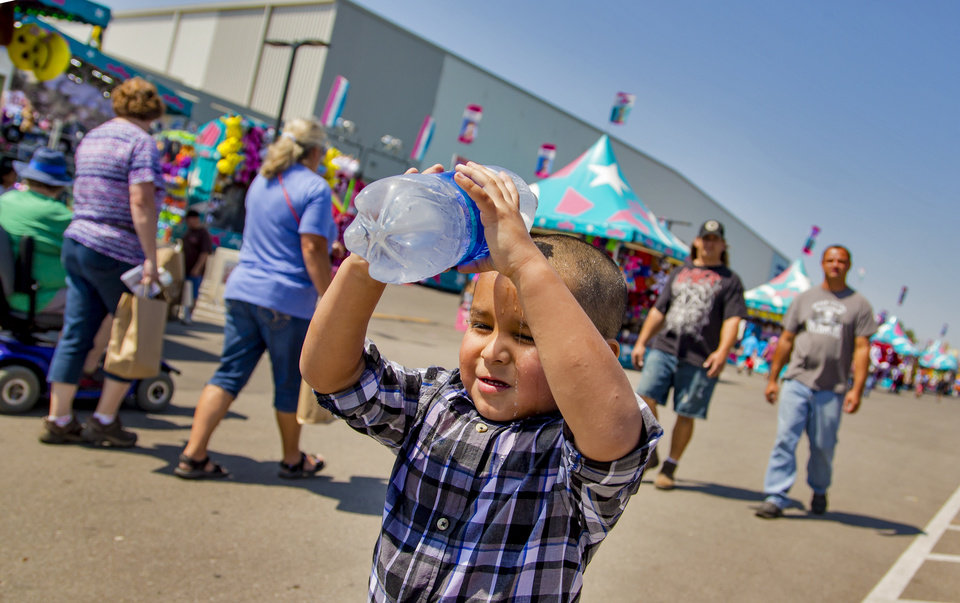 Photo - Travis Harjo, 3, cools himself off with a splash of water as he walks the midway during the opening day of the 2017 Oklahoma State Fair in Oklahoma City, Okla. on Thursday, Sept. 14, 2017. Photo by Chris Landsberger, The Oklahoman