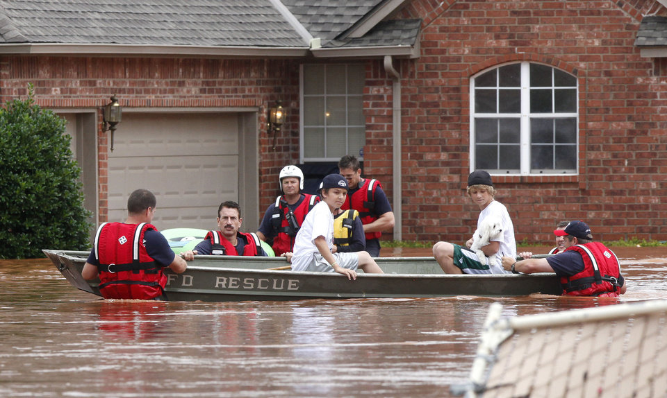 Photo - FLASH FLOODS / TORRENTIAL RAIN / THE VALLEY HOUSING ADDITION / RAIN / FLOOD / FLOODING: Oklahoma City Fire Department. rescue crews take 2 boys and their dog to higher ground in the Valley Addition in Edmond, OK, after flood waters inundated a number of homes in the area, Monday, June 14, 2010. By Paul Hellstern, The Oklahoman ORG XMIT: KOD