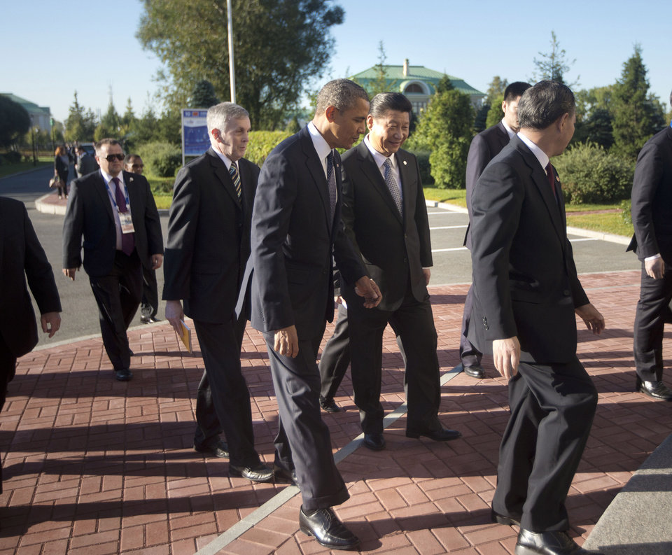 Photo - U.S. President Barack Obama, left, and China's President Xi Jinping, right, walk in together before participating in their bilateral meeting at the G20 Summit, Friday, Sept. 6, 2013 in St. Petersburg, Russia. (AP Photo/Pablo Martinez Monsivais)