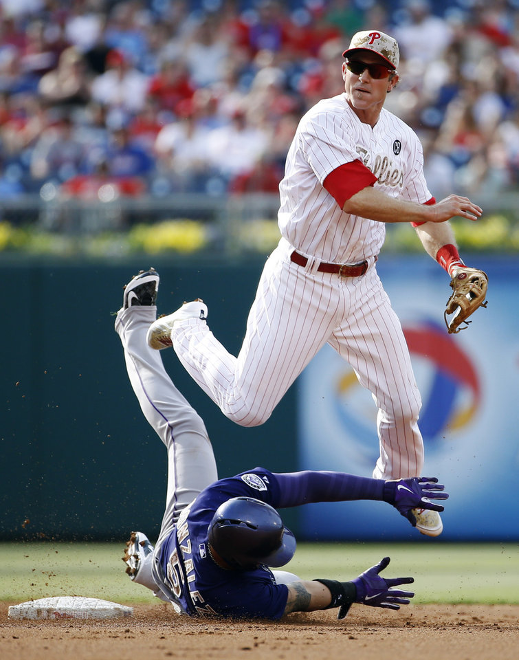 Photo - Philadelphia Phillies second baseman Chase Utley, right, leaps over Colorado Rockies' Carlos Gonzalez after forcing him out at second on a double play hit by Wilin Rosario during the second inning of a baseball game, Monday, May 26, 2014, in Philadelphia. Wilin was out at first on the play. (AP Photo/Matt Slocum)