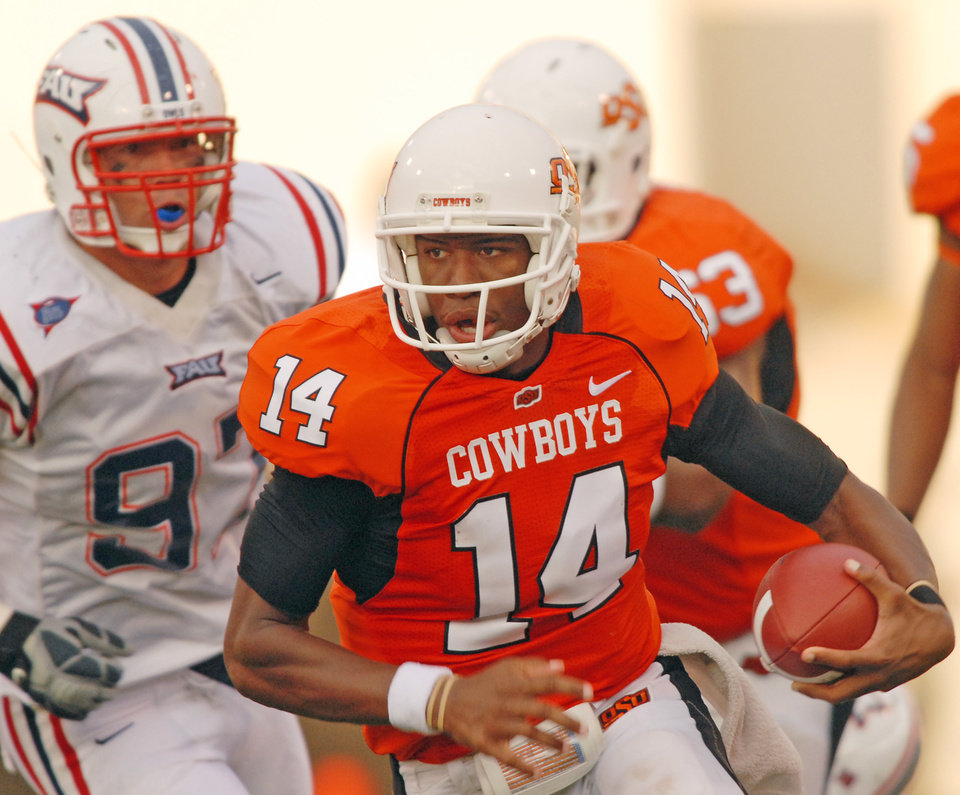 Photo - OKLAHOMA STATE UNIVERSITY, OSU vs. FLORIDA ATLANTIC UNIVERSITY: Oklahoma State quarterback Bobby Reid outruns Florida Atlantic defensive lineman Josh Pinnick during the first half of a football game in Stillwater, Okla., Saturday, Sept. 8, 2007. Reid had 32 yards rushing in Oklahoma State's 42-6 win over Florida Atlantic. (AP Photo/Brody Schmidt) ORG XMIT: OKBS103