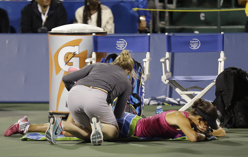 Photo - Ana Ivanovic, from Serbia, bottom, is tended to by a trainer during the second set of her match against Serena Williams in the Bank of the West Classic tennis tournament in Stanford, Calif., Friday, Aug. 1, 2014. Williams won 2-6, 6-3, 7-5. (AP Photo/Jeff Chiu)
