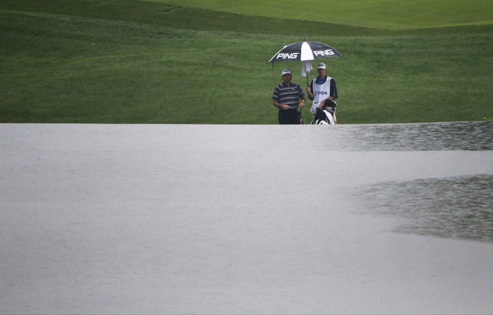 Photo - Bubba Watson watches as rain falls on the late along the 18th hole during the second round of the PGA Championship golf tournament at Valhalla Golf Club on Friday, Aug. 8, 2014, in Louisville, Ky. (AP Photo/Mike Groll)