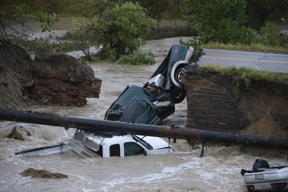 Photo - Three vehicles crashed into a creek after the road washed out from beneath them near Dillon Rd. and 287 in Broomfield Colo., Thursday, Sept. 12, 2013 in heavy flooding. Three people were rescued. (AP Photo By Andy Cross/The Denver Post)  MAGS OUT; TV OUT; NO INTERNET; NO SALES, MANDATORY CREDIT