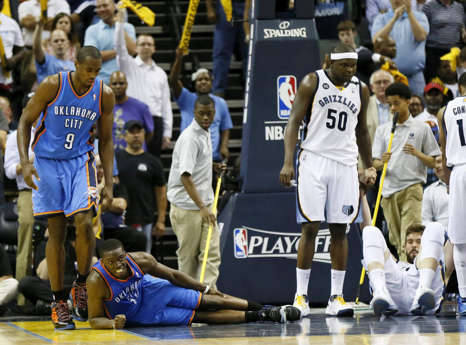 Photo - Oklahoma City's Reggie Jackson (15) is slow to get up next to Serge Ibaka (9) after falling to the court on a charge against Memphis' Marc Gasol (33), right, next to Zach Randolph (50) in overtime of Game 4 of the second-round NBA basketball playoff series between the Oklahoma City Thunder and the Memphis Grizzlies at FedExForum in Memphis, Tenn., Monday, May 13, 2013. Memphis won 103-97 in overtime. Photo by Nate Billings, The Oklahoman