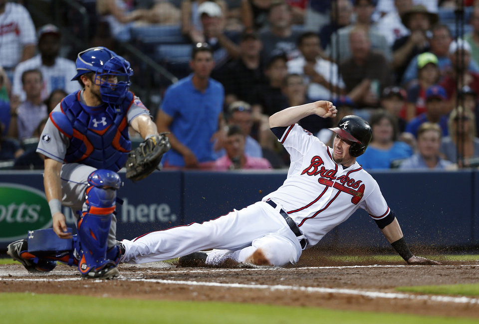 Photo - Atlanta Braves' Chris Johnson (23) scores on a Mike Minor base hit as New York Mets catcher Travis d'Arnaud (15) handles the late throw in the fourth inning of a baseball game in Atlanta, Tuesday, July 1, 2014.  (AP Photo/John Bazemore)