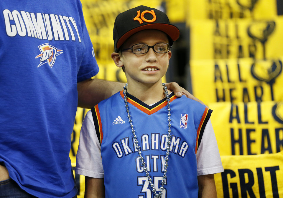 Photo - 11-year-old Thunder fan Austin Byrom of Fayetteville, Ark., watches the Thunder warm up with his father, Steve Byrom, before Game 4 of the second-round NBA basketball playoff series between the Oklahoma City Thunder and the Memphis Grizzlies at FedExForum in Memphis, Tenn., Monday, May 13, 2013. Photo by Nate Billings, The Oklahoman