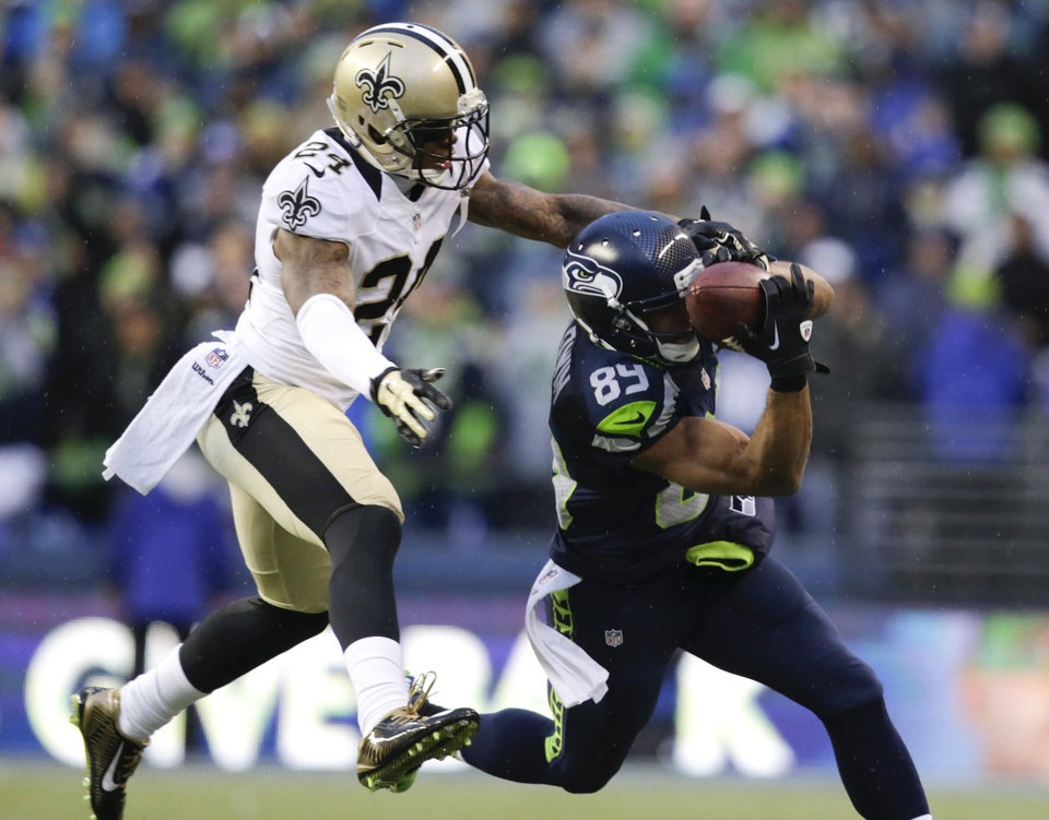 Photo - Seattle Seahawks wide receiver Doug Baldwin, right, catches a pass against New Orleans Saints cornerback Corey White during the fourth quarter of an NFC divisional playoff NFL football game in Seattle, Saturday, Jan. 11, 2014. The Seahawks won 23-15. (AP Photo/John Froschauer)