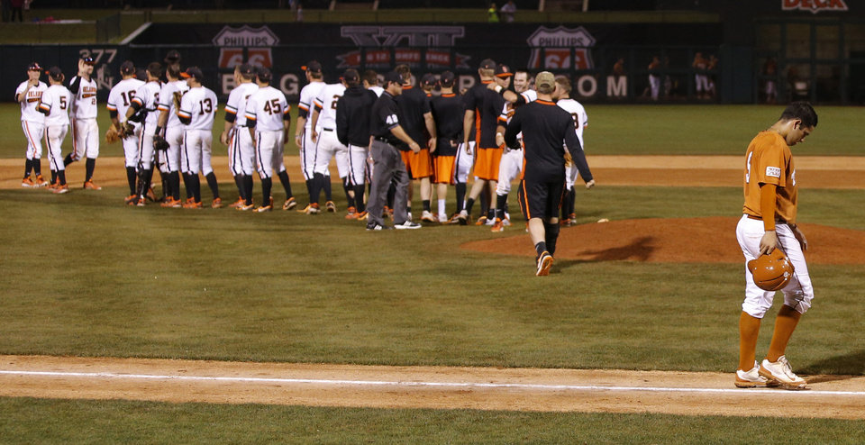 Photo - Texas' C.J. Hinojosa walks off the field after losing to OSU in a Big 12 Tournament baseball game between Oklahoma State University and the University of Texas at Chickasaw Bricktown Ballpark in Oklahoma City, Saturday, May 24, 2014. Photo by Bryan Terry The Oklahoman