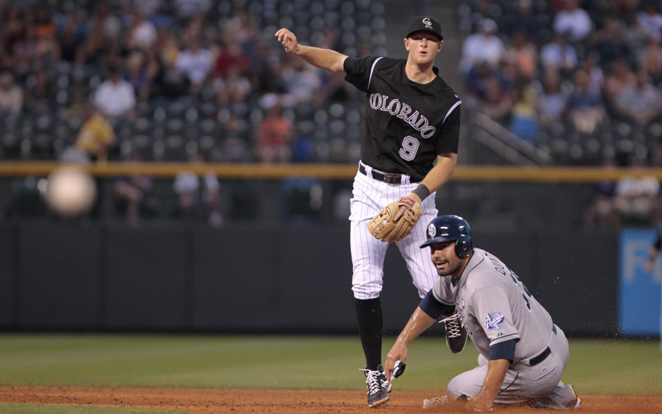 Photo - Colorado Rockies second baseman DJ LeMahieu (9) and San Diego Padres' Carlos Quentin (18) watch the ball arrive at first after Quentin was forced out at second base on a double play in the sixth inning of a baseball game in Denver on Tuesday, July 8, 2014. San Diego Padres' Tommy Medica (14) was out at first. (AP Photo/Joe Mahoney)
