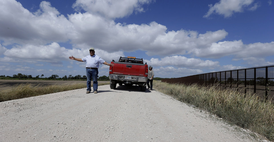 "In this Sept. 6, 2012, photo, cotton farmer Teofilo ""Junior"" Flores, left, with his wife, Maria Flores, talks about the U.S.-Mexico border fence that passes through his property in Brownsville, Texas. Since 2008, hundreds of landowners on the border have sought fair prices for property that was condemned to make way for the fence, but many of them received initial offers that were far below market value. (AP Photo/Eric Gay)"
