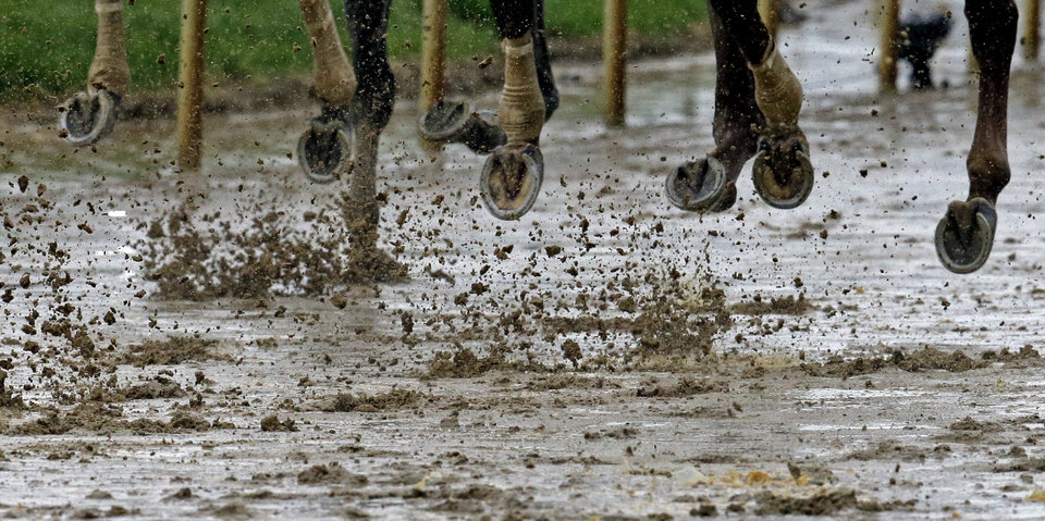 Horses run around a muddy track during the ninth race before the 139th Kentucky Derby at Churchill Downs Saturday, May 4, 2013, in Louisville, Ky. (AP Photo/J. David Ake)
