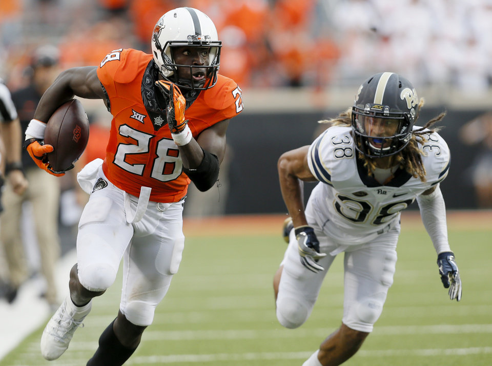 Photo - Oklahoma State's James Washington (28) runs after a reception as Pittsburgh's Ryan Lewis (38) chases him in the third quarter during a college football game between the Oklahoma State Cowboys (OSU) and the Pitt Panthers at Boone Pickens Stadium in Stillwater, Okla., Saturday, Sept. 17, 2016. Photo by Sarah Phipps, The Oklahoman