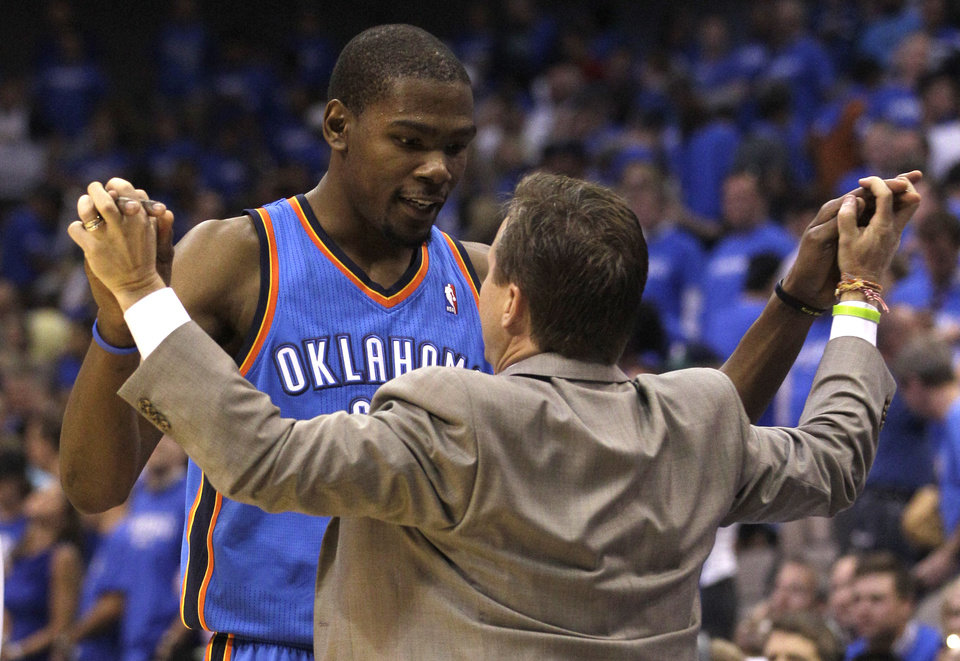 Photo -   Oklahoma City Thunder Kevin Durant, left, celebrates with head coach Scott Brooks in the final seconds of Game 4 in a first-round NBA basketball playoff series against the Dallas Mavericks, Saturday, May 5, 2012, in Dallas. The Thunder won 103-97. (AP Photo/LM Otero)