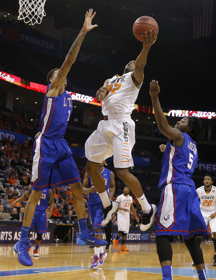 Photo - Oklahoma State's Markel Brown (22) goes to the basket between Louisiana Tech's Michale Kyser (1) and Chris Anderson (5) during the All-College Classic basketball game between Oklahoma State University and Louisiana Tech at Chesapeake Energy Arena in Oklahoma City, Okla., Saturday, Dec. 14, 2013. Photo by Bryan Terry, The Oklahoman