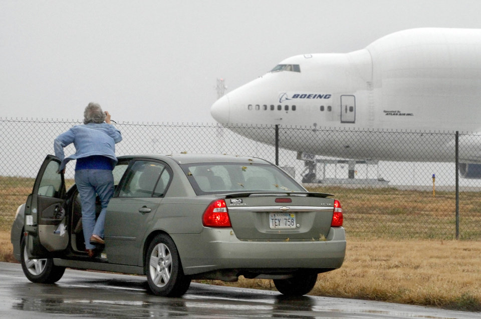 Photo - A woman tries to take a photo of a Boeing 747 Dreamlifter Thursday, Nov. 21, 2013, that mistakenly landed at Col. James Jabara Airport in Wichita, Kan. The jet landed Wednesday evening at the airport, about 8 miles (13 kilometers) north of its intended target, the McConnell Air Force Base. (AP Photo/The Topeka Capital Journal, Chris Neal)