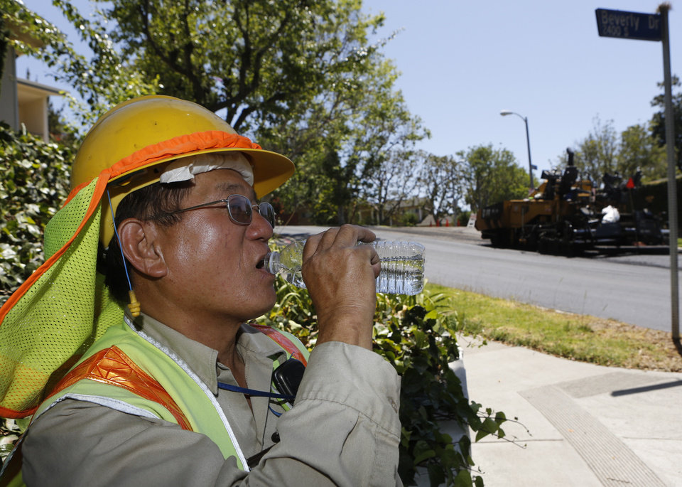 Photo - Los Angeles City Street Services Field Engineering Aide, Winston Chu drinks cold water as his crew paves streets under a heat wave in the Beverlywood neighborhood in Los Angeles, Tuesday, May, 13, 2014. An unseasonable spring heat wave is building in California under the influence of a high pressure system that is sending air rushing towards the coast and offshore. (AP Photo/ Damian Dovarganes)