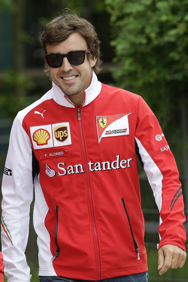 Photo - Ferrari driver Fernando Alonso of Spain walks at the paddock before a practice session ahead of Sunday's Chinese Formula One Grand Prix at Shanghai International Circuit in Shanghai, China, Friday, April 18, 2014. (AP Photo/Alexander F. Yuan)