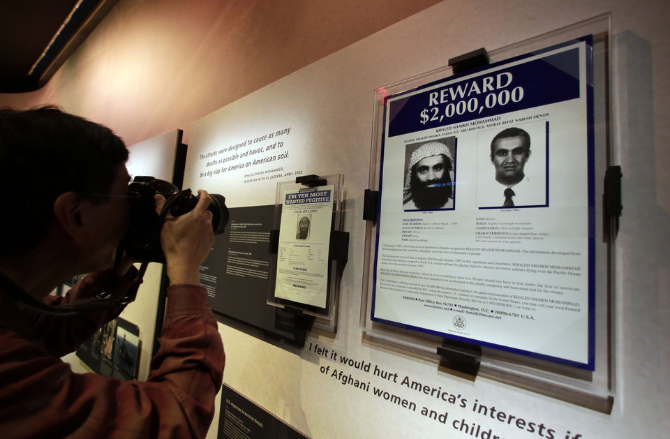 Photo - The wanted posters of Osama Bin Laden, left, and Khaled Shaikh Mohammad are displayed at the National Sept. 11 Memorial Museum, Wednesday, May 14, 2014, in New York. The museum is a monument to how the Sept. 11 terror attacks shaped history, from its heart-wrenching artifacts to the underground space that houses them amid the remnants of the fallen twin towers' foundations. It also reflects the complexity of crafting a public understanding of the terrorist attacks and reconceiving ground zero.  (AP Photo)