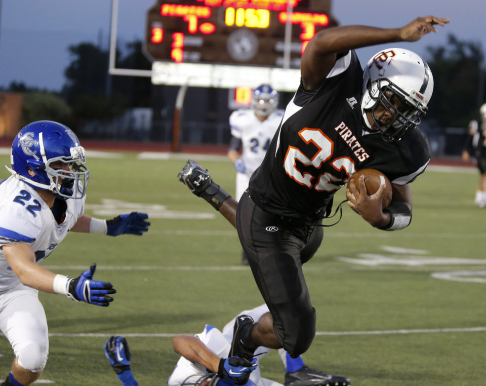 Putnam City\'s Denzel Dean leaps past Sapulpa\'s Corey Mondier during their high school football game at Putnam City in Oklahoma City, Thursday, Sept. 26, 2013. Photo by Bryan Terry, The Oklahoman