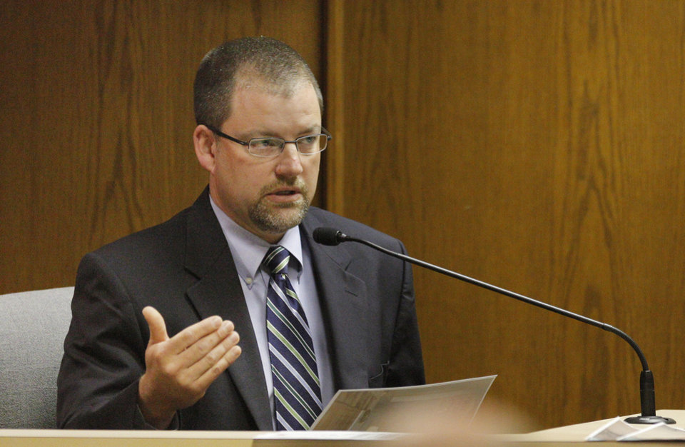Photo - Oklahoma State Bureau of Investigation agent Shawn Wright holds a photograph while testifying Wednesday during the preliminary hearing for Rebecca Bryan at the Canadian County Courthouse.