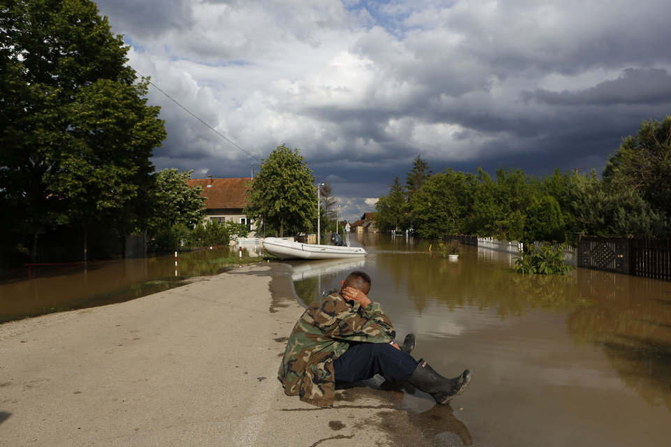 Photo - A Bosnian man sits on the edge of the water in the village of Vidovice near Orasje 200 kms north of Sarajevo, on Sunday May 18, 2014. Packed into buses, boats and helicopters, carrying nothing but a handful of belongings, tens of thousands fled their homes in Bosnia and Serbia, seeking to escape the worst flooding in a century. (AP Photo/Amel Emric)
