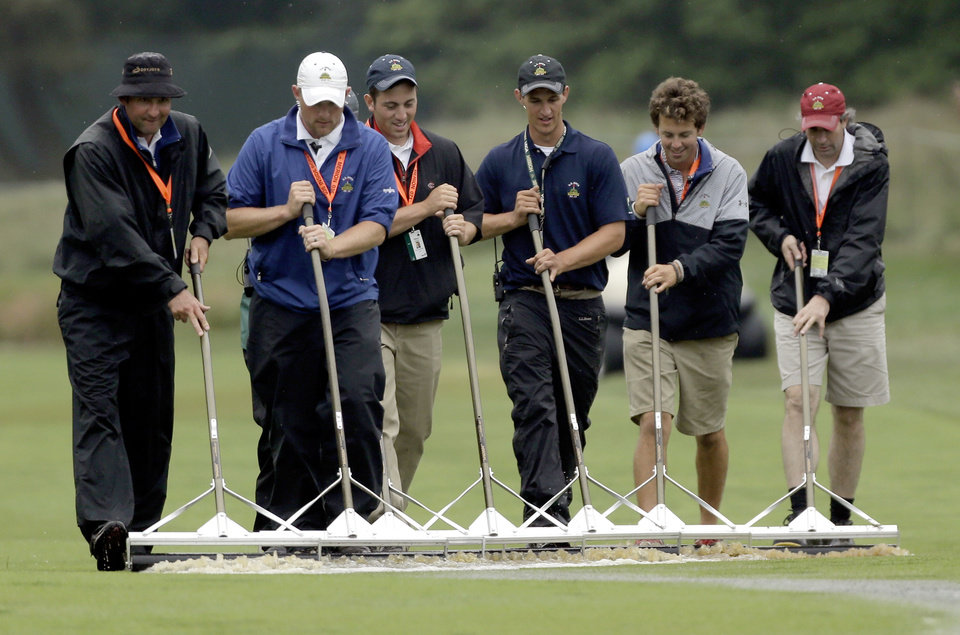 Photo - Course workers clear water from the sixth fairway after a weather delay during the first round of the U.S. Open golf tournament at Merion Golf Club, Thursday, June 13, 2013, in Ardmore, Pa. (AP Photo/Julio Cortez)