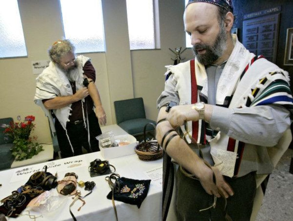Photo - Rabbi Russell Fox, right,  shows Len Capps, of Del City, and other members of Emanuel Synagogue, 900 NW 47, how to put on tefillin in this 2008 photo. Photo by John Clanton, The Oklahoman Archive.  JOHN CLANTON - THE OKLAHOMAN