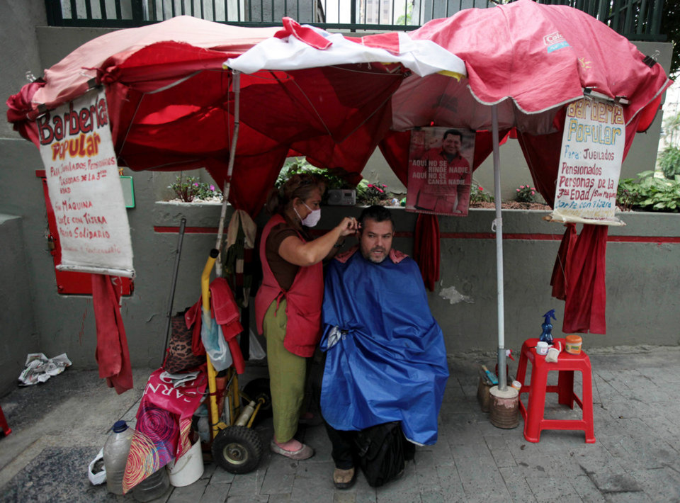 Photo - A man gets his hair cut at a street barbershop decorated with a images of Venezuela's President Hugo Chavez in downtown Caracas,Venezuela, Tuesday, Dec. 11, 2012. Chavez was preparing to undergo a new cancer surgery on Tuesday in Cuba, his government said, after his illness reappeared despite a year and a half of surgeries and treatments. The Venezuelan president announced on Saturday that he needed to undergo a fourth cancer-related surgery after tests showed that