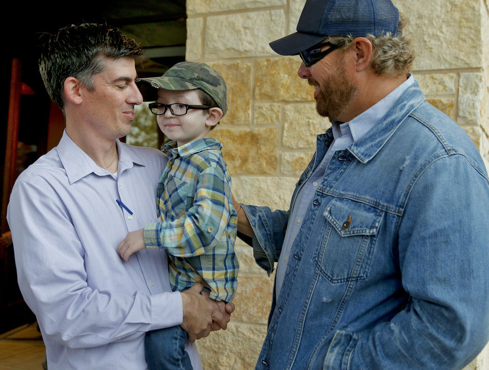 Photo - Toby Keith, right, talks with cancer patient Brock Hart, 5, and his father Jay during the grand opening of the Toby Keith Foundation's OK KIds Korral in Oklahoma City, Okla. on Thursday, Nov. 21, 2013. The Toby Keith Foundation was established to help children stricken with  cancer. The work has led to the construction of the OK Kids Korral as a home-away-from home in Oklahoma City for pediatric cancer patients. Photo by Chris Landsberger, The Oklahoman
