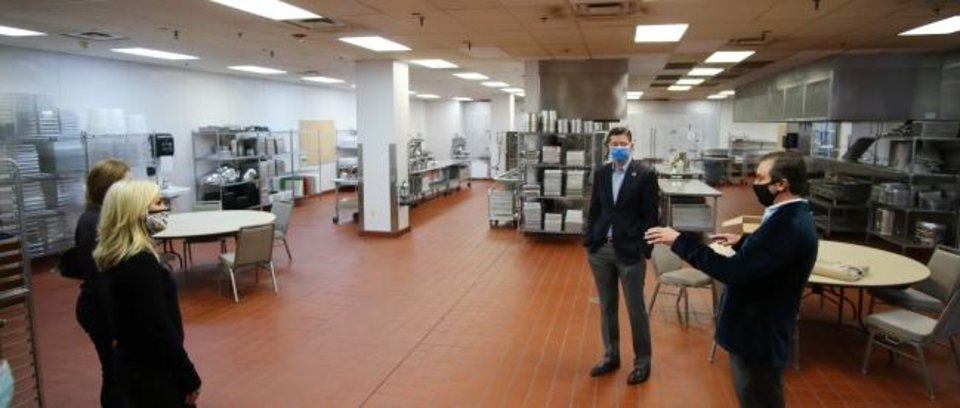Photo -  Rachel Cannon and Matt Payne  (shown left and right), cofounders of  Prairie Surf Media, tour the large commercial kitchen that is one of the selling points for converting the Cox Convention Center into a space to be used for sound stages and production. Mayor David Holt is show in the center with Assistant City Manager standing behind Cannon. [DOUG HOKE/THE OKLAHOMAN}