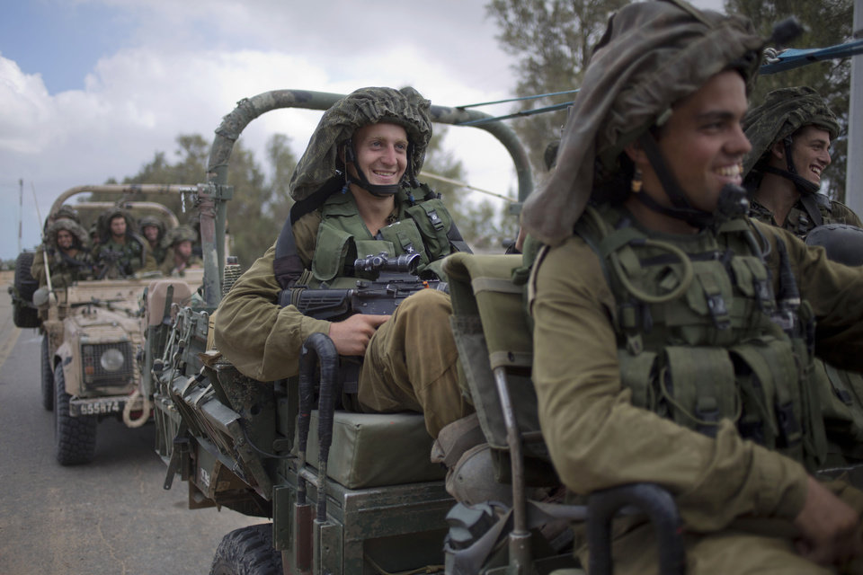 Photo - Israeli soldiers smile as they ride on a military vehicle near the Israel-Gaza Border, Thursday, July 17, 2014. Israel and Hamas have begun observing a five-hour humanitarian cease-fire, as fighting extended into a 10th day. The two sides agreed to the pause following a request by the United Nations so that supplies could be delivered to Gaza.(AP Photo/Ariel Schalit)