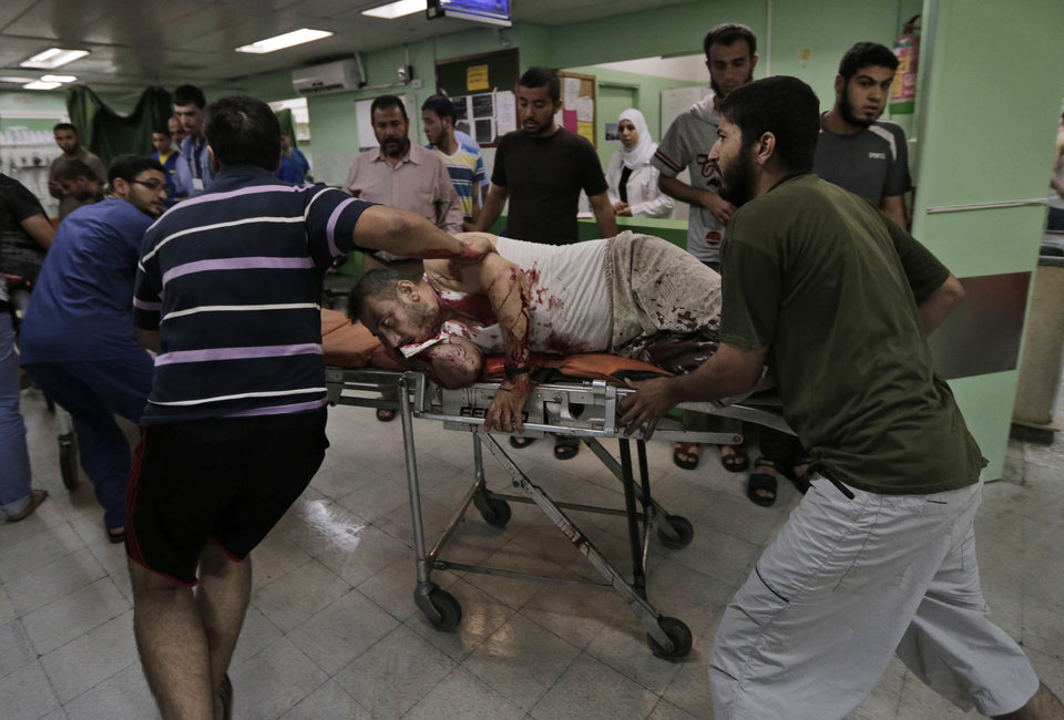 Photo - A Palestinian, wounded in an Israeli strike at a house in Beit Lahiya, northern Gaza Strip, is wheeled into the emergency room of the Kamal Adwan Hospital, in Beit Lahiya, Sunday, Aug. 3, 2014. (AP Photo/Lefteris Pitarakis)