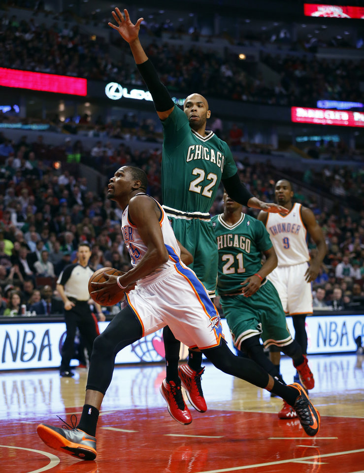 Photo - Oklahoma City Thunder forward Kevin Durant, left, goes to the basket past Chicago Bulls forward Taj Gibson (22) during the first half of an NBA basketball Monday, March 17, 2014, in Chicago.  (AP Photo/Jeff Haynes)